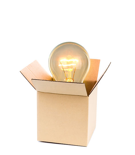 Glowing light bulb over open cardboard b