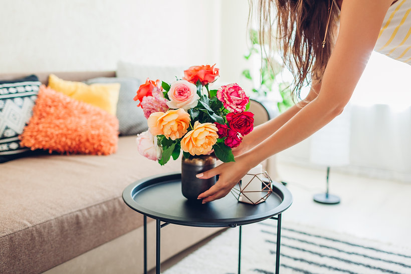 Woman puts vase with flowers roses on ta