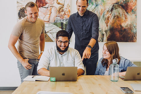 Colleagues in the office laughing and smiling while working together as a team