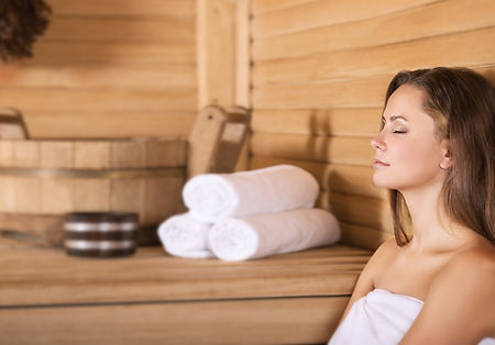 Woman lookin relaxed in sauna with eyes closed towels and bucket are placed behind her