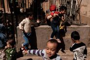Kashgar. Xinjiang Uyghur. Kids running around street.