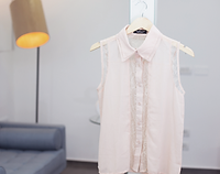 White sleeveless button up hanging
