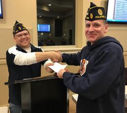Ed Behrens receives a Volunteer Award from Commander Mike Klanang.