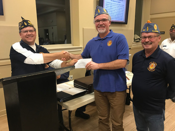 Sons of the American Legion representatives, Finance Officer Jim Steiner and Chaplin John Nemanich, present Commander Mike Klanang with a check for proceeds from the 2019 Oktoberfest. The proceeds will be used to support veterans programs.