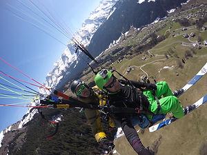 Une photo prise en vol tandem en parapente au Grand Bornand, avec les skis aux pieds