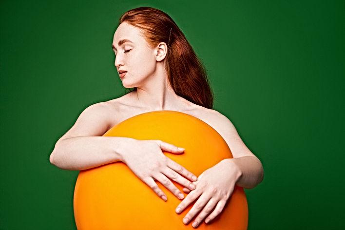 Menina que abraça a esfera alaranjada