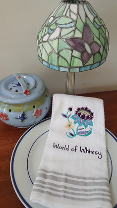 Kitchen towel with imbroidered of World of Whimsy design.