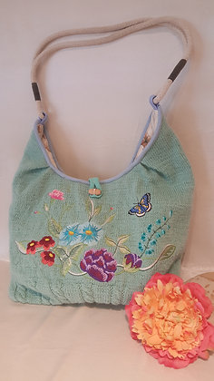 Knitted bag with imbroidered flower design.