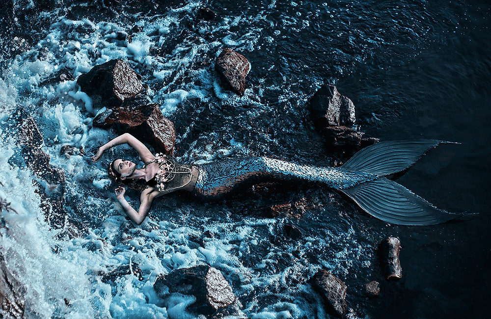Photo composite of a mermaid lying back in shallow water, with rocks around her. Her arms are over her head as she looks into the sky.