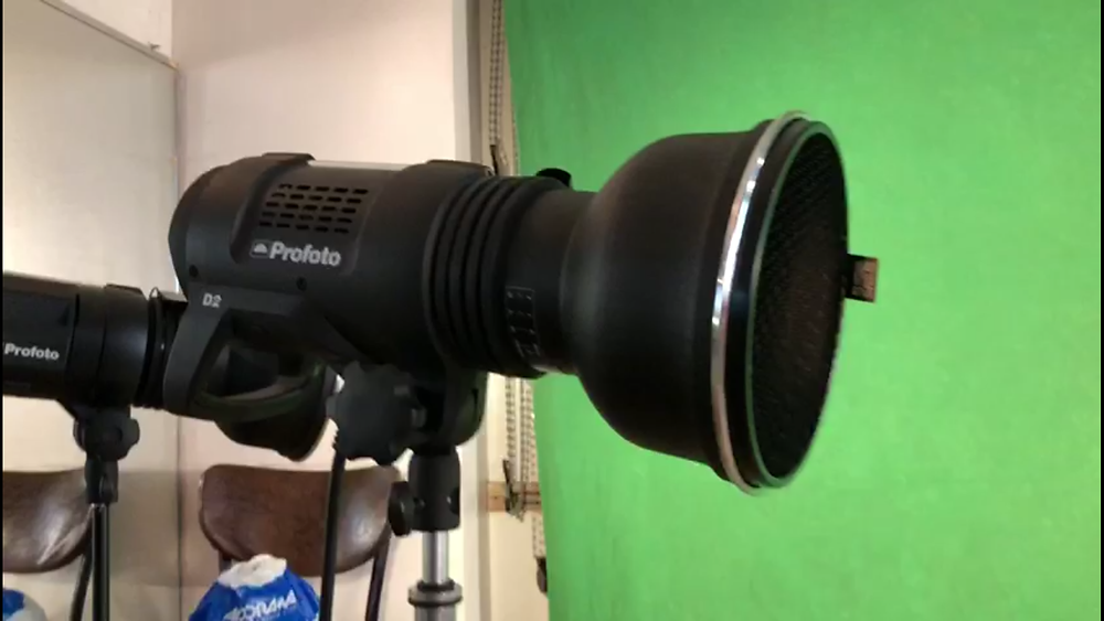 This 2nd studio strobe with a grid on it is placed to light the model, as a subtle fill to the main light.