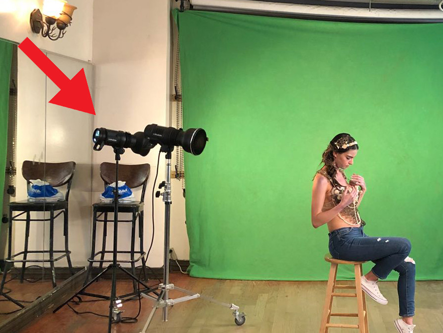 Here we have an image of a photo studio with a green screen backdrop. There's a red arrow above one of the studio strobes indicating that this is the strobe that will light the backdrop