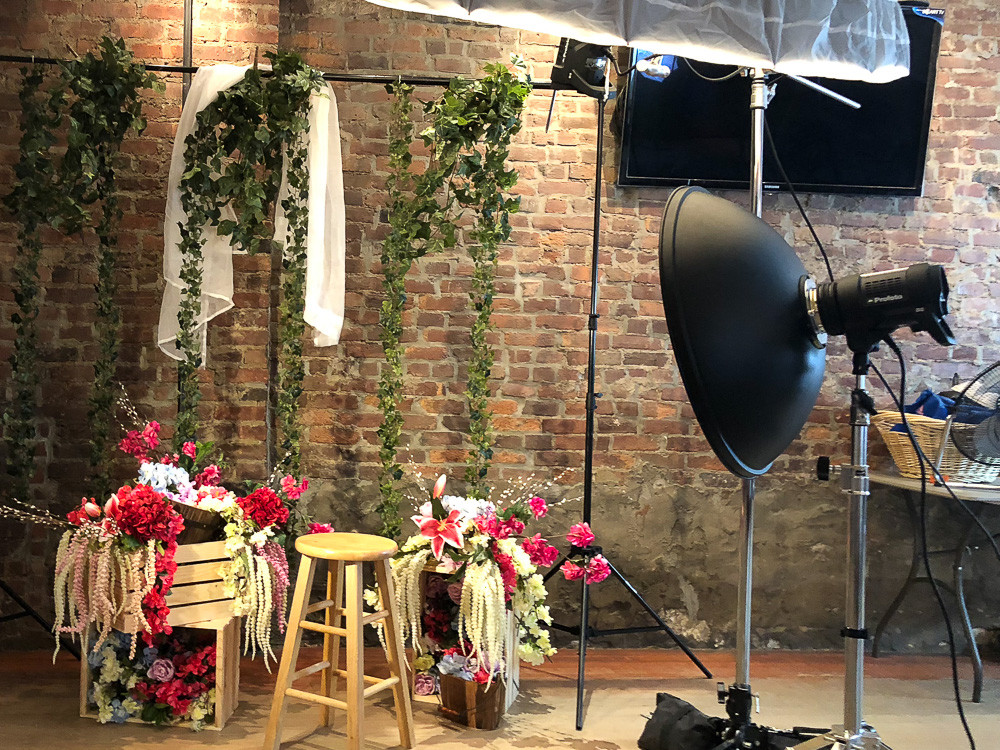 This is a photo of a floral editorial, with fake vines and flowers draped over a portable stand.  There's a studio strobe showing how it is going to light up the model, as she's sitting on the stool.
