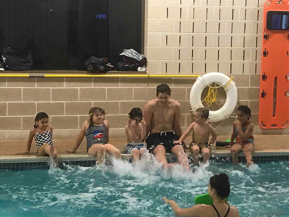 Swim School Coach James teaches his swimmers how to flutter kick in their swim lessons.