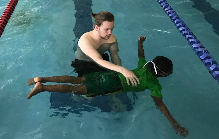 Local swim instructor teaches a child how to float on his stomach.