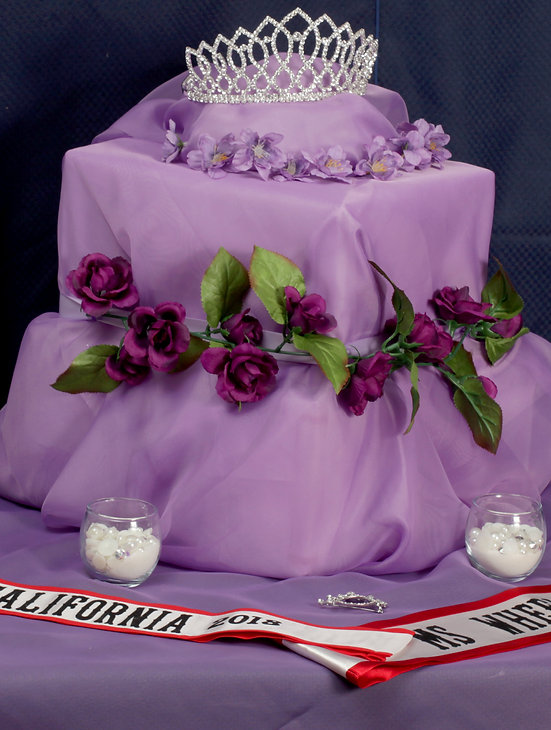 Photo of a crown on a purple platform, with purple roses, and the MWCA 2018 red and white sash.