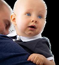 Un bébé dans les bras de son père regarde vers nous