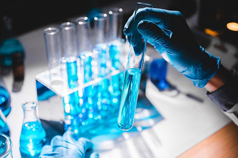 hand-in-blue-glove-holding-vial-of-blue-