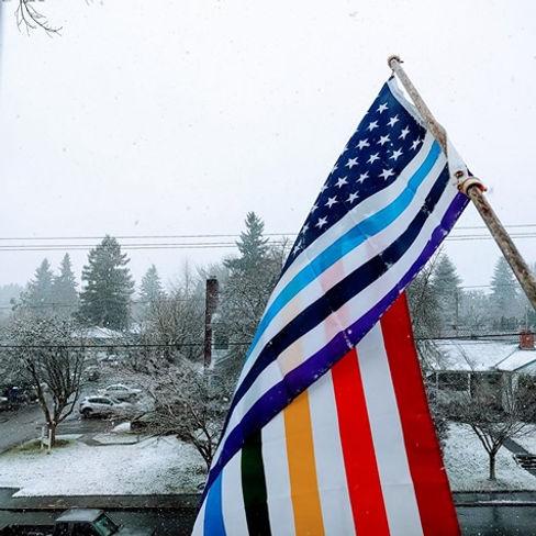 Rainbow striped US flag against snowy background