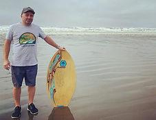 Man wearing shirt at alki beach holding boogie board.
