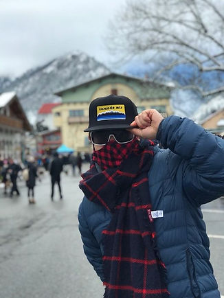 dad in cascade mountains flat billed cap hat wearing sunglasses and scarf in winter during Leavenworth vacation.