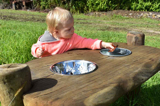 Child playing on a sand table mud kitchen