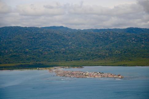 """Le territoire Kuna, appelé le """"Comarca Kuna Yala"""", est une division administrative du Panama. Il comprend les 365 îles de l'archipel des San Blas, dans la mer des Caraïbes, et une bande côtière de 5 à 10 km de large s'étendant sur plus de 200 km de long. Ces îles sont situées à quelques centaines de mètres, voire quelques kilomètres, seulement du continent. Les Kuna peuvent ainsi se rendre facilement sur la terre ferme pour y faire de l'agriculture. Ils vivent en communautés, 45 d'entres elles vivent sur les îles, tandis que seulement 4 vivent encore dans la forêt, sur le continent. Sur cette photo, l'île est reliée au continent par un pont. Au-delà des zones exploitées pour l'agriculture, c'est la forêt primaire."""