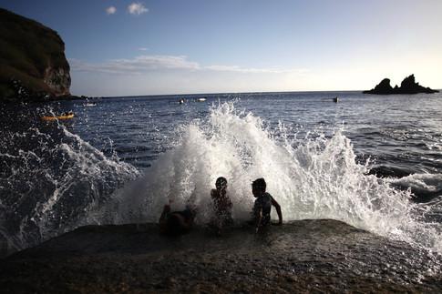 Sur la cale de mise à l'eau d'Hakamaii, les enfants s'amusent à défier les vagues. Celle-ci, particulièrement grosse, semble être celle qu'ils attendaient.
