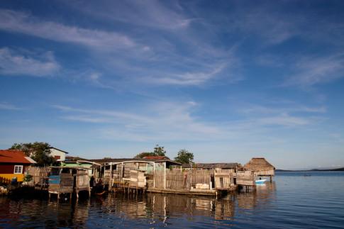 Un soir sur la jetée.  Le ciel est dégagé, ce qui est assez rare en cette saison des pluies. Nous observons longuement le littoral et les enfants qui jouent dans les pirogues. Les maisons sont construites juste au bord de l'eau. Certaines parties de l'île ont été gagnées sur la mer pour permettre l'installation de nouvelles maisons, car la population augmente.