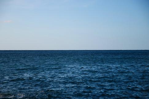 Ce soir là, nous nous trouvons au bout du quai pour réaliser quelques plans de la zone de l'Aire Marine Éducative.  La lumière est belle, à droite, on a une bonne visibilité sur les côtes de Nuku Hiva.  En face, l'Océan Pacifique, d'un bleu cobalt, à perte de vue.