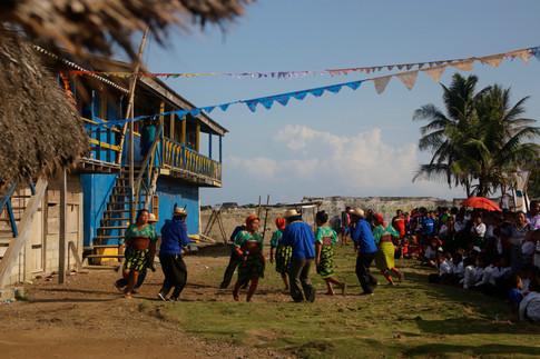 Une représentation de danse et de musique kuna lors d'une fête de village, en l'honneur de l'un des instigateurs de la révolution de 1925. Les femmes battent la mesure avec des maracas, tandis que les hommes jouent de la flûte de Pan.