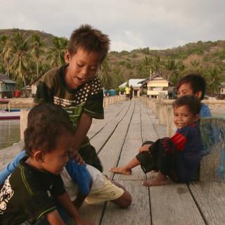Le soleil se couche, les garçons courent et se bagarrent sur le ponton.