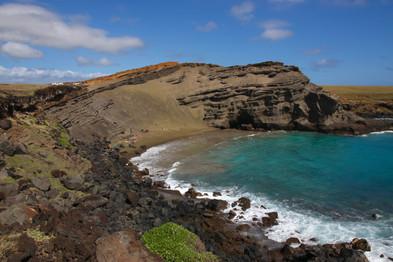 La plage de sable vert de Papakolea.   Cette couleur est due à l'olivine, un minéral vert présent dans les roches volcaniques.