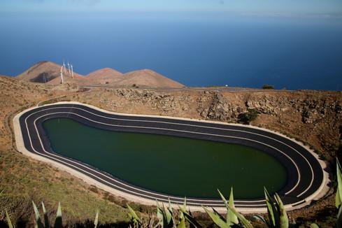 Au premier plan, le lac de retenue d'eau (eau de mer désalinisée), acheminée jusque dans les hauteurs de l'île avec des pompes, alimentées par le surplus d'électricité produite par les 5 éoliennes (au deuxième plan) qui fournissent une grande part de l'électricité de l'île. Lorsque le vent n'est pas assez constant ou assez fort pour faire tourner suffisament les éoliennes, des lâchés d'eau depuis ce lac permet d'assurer la production d'électricité sur l'île pendant quelques jours.