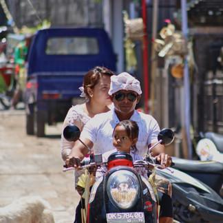 Dans les ruelles de Pecatu, durant la cérémonie de Galungan.  Les habitants se déplacent très régulièrement en scooter. Ils peuvent être parfois 4 sur ces engins. Il y a beaucoup de trafic à Bali, mais peu d'accidents. Chacun sait se respecter.