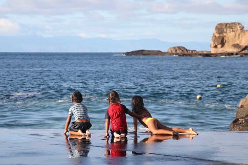 Les enfants d'Hakahetau attendent la vague qui va les faire glisser sur la calle de mise à l'eau.   Ils passent leurs journées à se baigner et reviennent chez eux les yeux rougis par le sel, à l'heure où le soleil se couche.