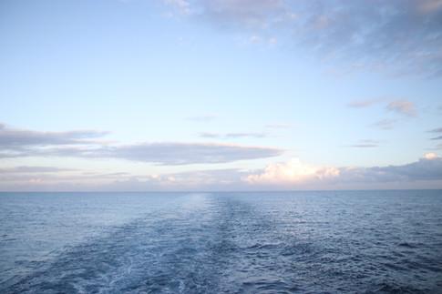 Après avoir longuement attendu et espéré, le bateau de croisière et de marchandises, l'Aranui, qui passait ce Lundi à Nuku Hiva a finalement pu nous accorder une place pour le trajet jusqu'à Tahuata. C'était inespéré, et c'était notre dernière chance pour rejoindre le festival.  Après une courte nuit, nous regardons le bateau s'approcher des côtes de Tahuata à l'aube.  Derrière, l'Océan Pacifique.