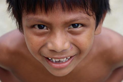 Un jeune Kuna dans les rues d'Ustupo.  Il a évité pendant longtemps de se faire photographier, mais au bout d'un moment, il finit par s'approcher, curieux, amusé. Je lui montre des photos et se sent alors fier de poser. Il m'adresse sont plus beau sourire.
