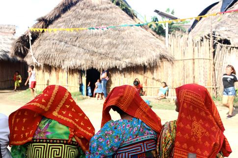 Au premier plan: des femmes venues assister au spectacle de danse.  En arrière plan, une maison traditionnelle Kuna, fait en bois de mangroves (ossature), en bois de canne à sucre (murs) et en feuilles de palmiers (toiture).