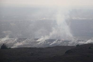 Paysage lunaire au coeur du Hawaian Volcanoes National Park. La gigantesque caldeira du Kilauea, un monstre effusif en activité depuis 30 ans.  La fumée sort du cratère Halemaumau qui est en fait un véritable lac de lave en ébullition.  Il existe un autre cratère sur les flans du Kilauea, d'où s'échappe la lave qui coule vers l'océan.  Au dessus de lui, dans les nuages, veille le Mauna Loa, un volcan endormi de plus de 4000m d'altitude (dernière éruption en 1984).   De ces deux volcans est née l'île d'Hawaii il y a 400 000 ans.