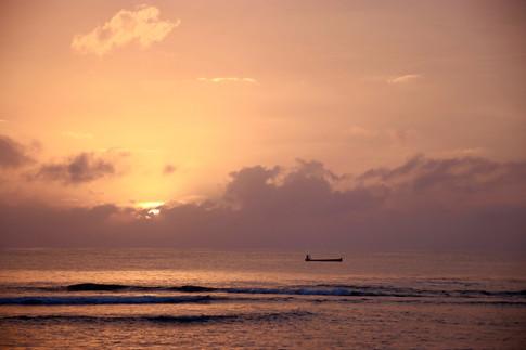 Le soleil se lève sur l'île d'Ustupo et un pêcheur s'n va au large.
