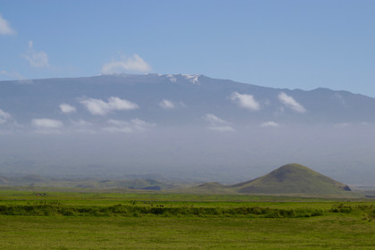 Les plaines du Ranch Parker de Waimea, où broutent les innombrables vaches noires. Ce matin, le ciel dégagé nous permet de voir le sommet enneigé du Mauna Kea, plus haut volcan du monde avec ses 4 205m. Volcan aujourd'hui endormi, son sommet abrite la plus grande base astronomique du monde.