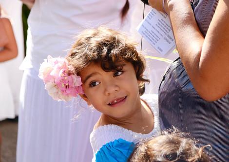 """Hakamaii. C'est la procession de la vierge Marie qui n'a lieu qu'une fois par an, dans différentes vallées.  Nombreux sont ceux qui sont venus assister à l'événement.  Il fait une douce chaleur que les alizés rendent agréable, les habitants son en blanc, les femmes en robes avec des colliers et couronnes de fleurs dans les cheveux.  Tous suivent Marie jusqu'à l'église en chantant des """"himene"""" religieux accompagnés des tambours, les """"pahu"""", et des ukulélés.   La religion occupe une place très importante dans la vie des Marquisiens.  Après la messe, il y aura des danses et un grand kaïkaï (repas communautaire) à base de poisson cru au lait de coco, chèvre au gingembre, riz, poisson grillé, cochon, poulet, manioc, taro, potiron au lait de coco et salades diverses.   Ici, Kumevevao s'accroche aux jambes de sa maman Emilienne, en attendant que la procession commence."""