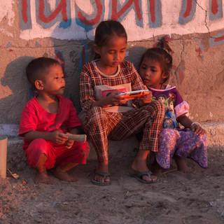 """Au crépuscule, alors que je me promène sur le port, Nasti joue avec quelques enfants à un jeu vidéo. Cette heure là correspond à une heure plus fraîche où les enfants, une fois lavés se retrouvent en pyjama à traîner entre eux dans les """"rues"""" de Seraya pendant que les mères et filles plus âgées préparent le poisson et le riz."""