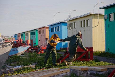 Après une partie de pêche, deux pêcheurs remontent leur bateau sur terre à l'aide du cabestan.