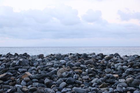 Ce soir là, le ciel est couvert de nuages.  Il y a toutes ces différentes teintes de gris entre le ciel, la mer, et les galets.  Ce sont les trois mondes symbolisés par le Ipu marquisien : le monde des cieux, le monde des vivants (la terre), et le monde des ancêtres et des dieux (la mer).
