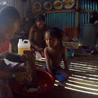 """La cuisine de la maison. Les femmes s'y retrouvent pour préparer les repas et nettoyer la vaisselle. L'eau s'écoule entre les planches du """"parquet"""" et viens abreuver, chèvres et poules se situant juste en dessous. Rini rape de la noix de coco pour la sauce qui servira au poisson qu'Awan prépare derrière elle. Safira, la regarde avec attention, tout en essayant de voler quelques bouts de noix de coco rapée par ci-par là."""
