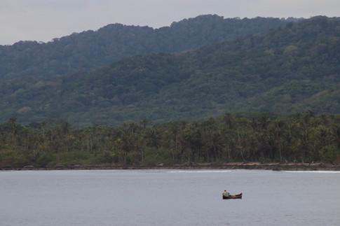 Un Kuna traverse en pirogue, à la rame, le bras de mer qui sépare l'île d'Ustupo du continent.
