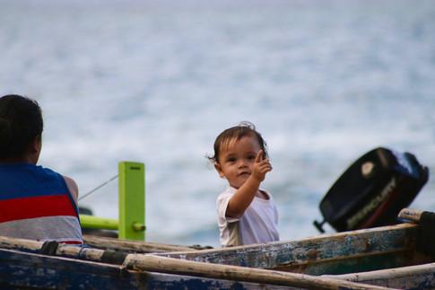 Hakahetau, un soir. Ce petit garçon a pris place à bord d'une pirogue, fin prêt pour la partie de pêche de nuit !