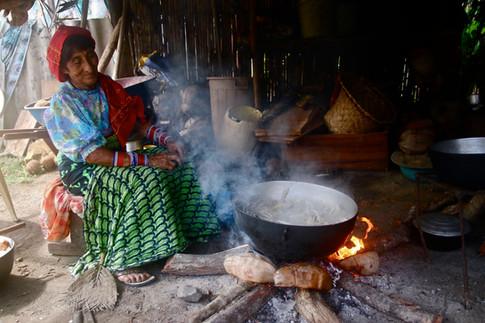 """Les femmes font la cuisine dans de petites huttes à côté de leurs maisons. Ici, un feu fait avec du bois ramené du """"campo"""" permet de faire cuire des crabes. Ils seront accompagnés d'une soupe de bananes plantain, de yuca et d'igname avec de la noix de coco rapée, du sel et du citron."""