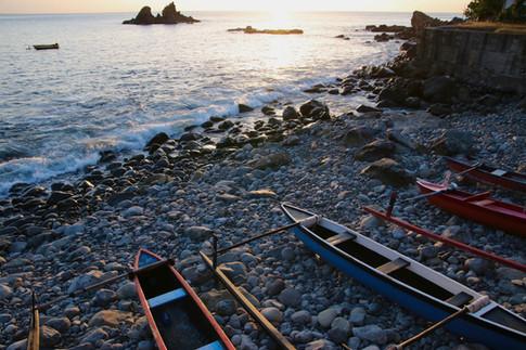 Littoral d'Hakamaii. Nous sommes venus passer l'après-midi dans une vallée à l'ouest d'Hakahetau.  Ici, nous pouvons voir le soleil se coucher sur l'océan.  Les pirogues sont bien rangées. Elles attendent les pêcheurs qui viendront, tôt le lendemain matin, les pousser jusqu'à la mer.   Ces pirogues à balancier, ressemblent fortement à celles que l'on trouve en Indonésie.  Il n'y a rien d'étonnant à cela, les descendants des polynésiens venaient d'Asie du Sud-Est !